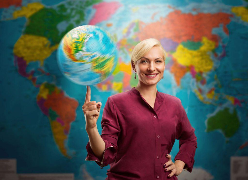 Mulher branca e loira com o cabeço preso em um coque e ela está usando uma camisa social cor de vinho. Ela está com uma mão na cintura e a outra está com o dedo indicador levantado equilibrando um globo terrestre e ao fundo há um mapa do mundo.