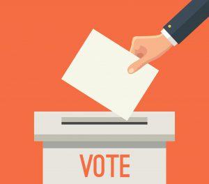 Desenho de uma caixinha branca com a palavra vote escrita em vermelho na parte da frente. Na parte de cima da caixa há uma abertura e um pouco acima há uma mão depositando um papel na caixa.