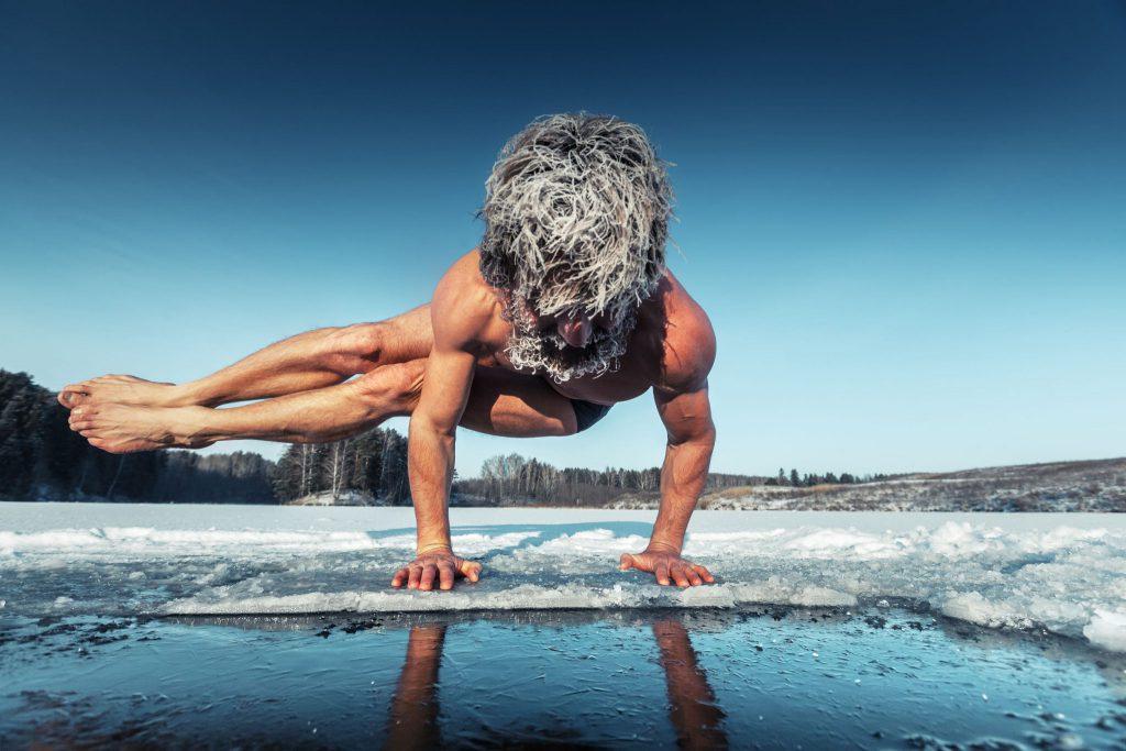 Homem apoiado em seus dois braços enquanto as duas pernas estão elevadas e viradas para a direita. Ele está em um ambiente cujo céu é azul escuro e o chão é de gelo.