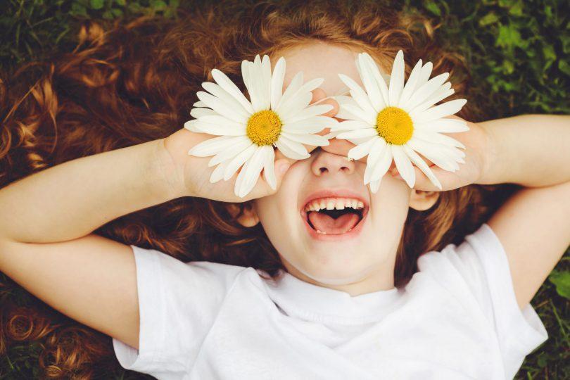 Menina de cabelos ruivos e encaracolados deita no chão. Ela está sorrindo e está segurando uma flor margarida em cada mão e as coloca na altura do olho.