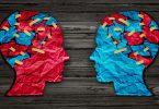 A forma de duas cabeças, uma virada de frente para a outra, feitas de papel. Uma é azul com pedaços de papel vermelho colado. A outra é vermelha com pedaços de papel azul colados.