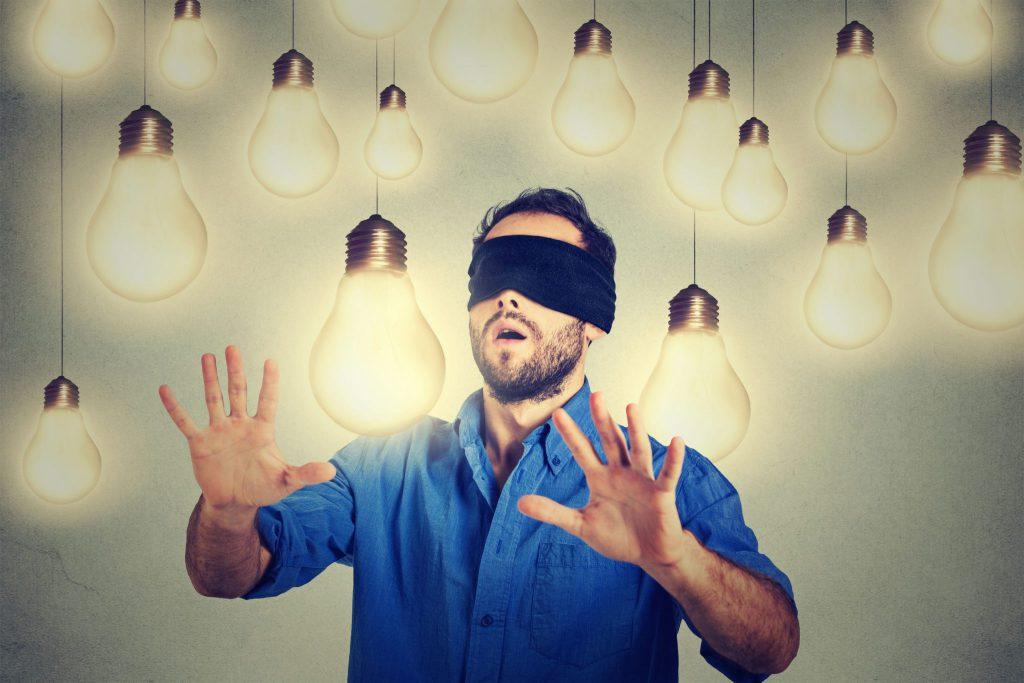 Homem vestido uma camisa azul. Ele está vendado com as mãos um pouco a frente de seu corpo e há diversas lâmpadas acesas e penduradas ao seu redor.
