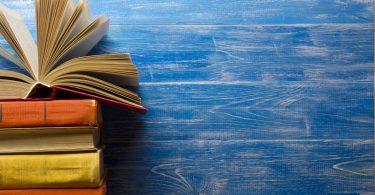 Pilha de livros na frente de uma parede azul com o livro de cima aberto.