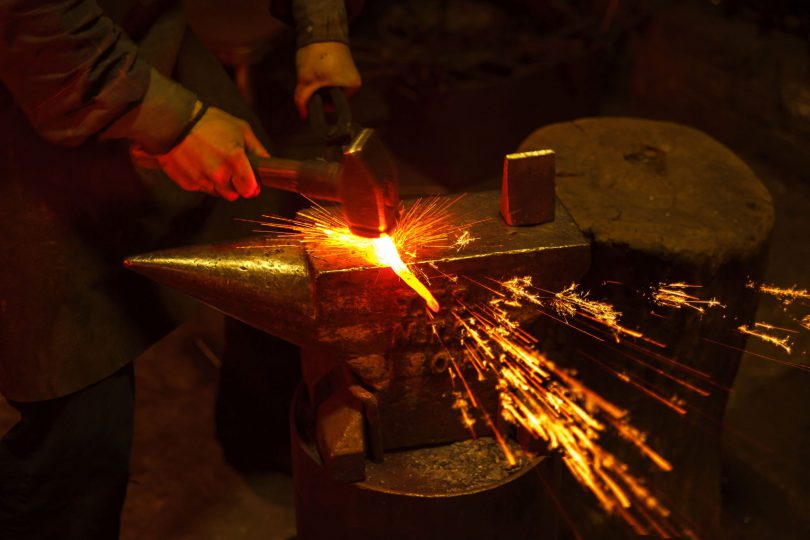 Mãos de um ferreiro manipulando ferro derretido.