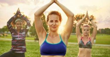 Três mulheres em posição de Yoga, com as mãos se tocando acima da cabeça. Há uma mulher no centro que é loira e está vestindo um top azul, a sua direita há uma mulher negra vestindo uma blusa de manda comprida preta com listras rosas, vermelhas e brancas. A esquerda há outra mulher loira vestindo um top verde musgo. Ao fundo há um fim de tarde, árvores e gramado.