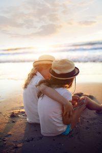 Duas meninas sentadas na areia da praia abraçadas. Elas estão usando um chapéu de palha e vestindo camisetas brancas de mangas curtas.
