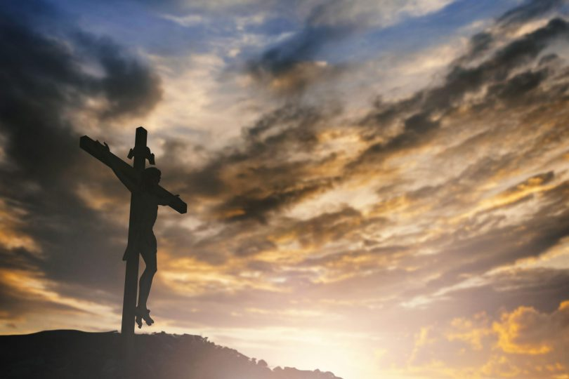 Imagem de um crucifixo em cima de um pequeno monte com um céu nublado ao fundo.