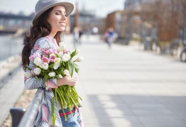 Mulher de olhos fechados, sorrindo, segurando um buquê de flores, enquanto atravessa a rua.