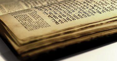 Foto desfocada mostra páginas envelhecidas da bíblia hebraica.