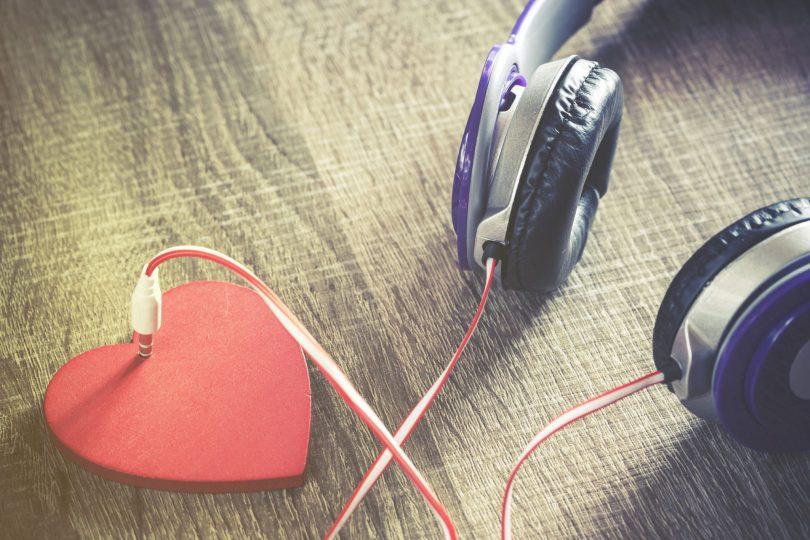 Fones de ouvido em cima de uma mesa, conectado à um coração.