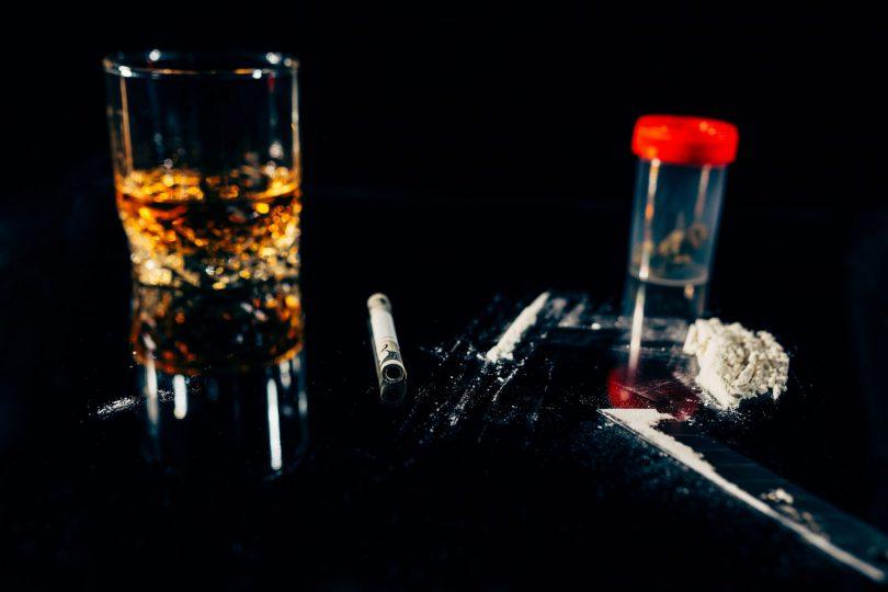 ´Copo de bebida, cigarro, remédios e drogas em cima de mesa e fundo pretos.