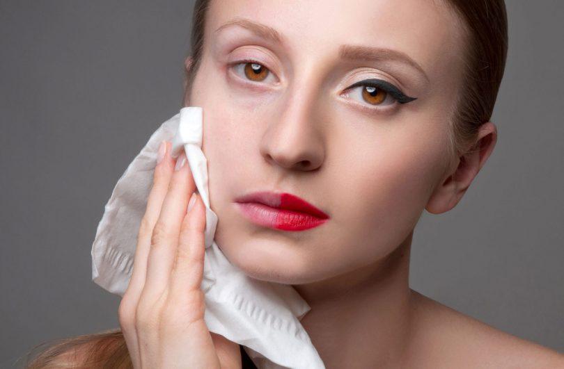Mulher branca com o cabelo preso para trás. Ela está pressionando um lenço umedecido contra o rosto, que está metade maquiado e a outra metade está natural. A mulher tem olhos castanhos.