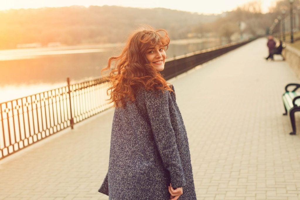 Mulher de cabelos castanhos avermelhados e cacheados que está virada levemente para trás e sorrindo. Seus cabelos estão esvoaçados com o vento. Ela está usando um casaco de mangas compridas e ao fundo há um rio.