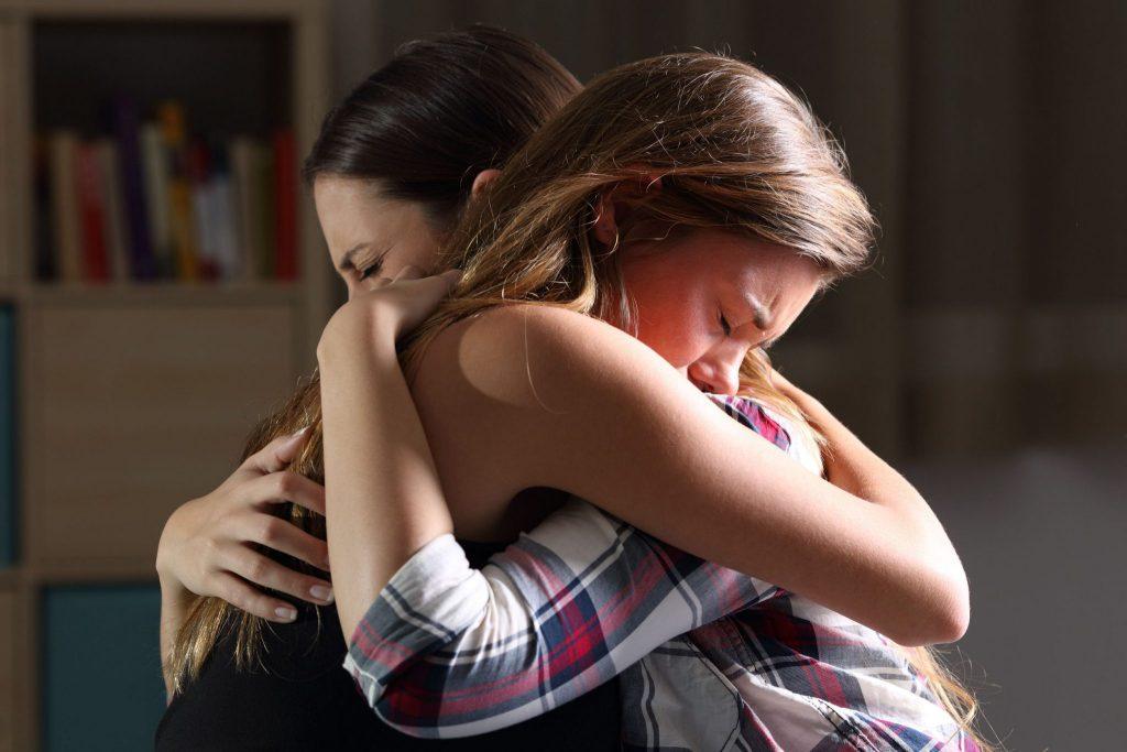 Duas mulheres se abraçando. Uma delas está de regata preta e tem cabelos longos, castanhos claro e liso. A outra está com uma camisa xadrez azul, vermelha e cinza claro, e tem cabelos castanhos e lisos.