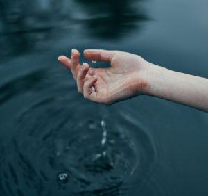 Mão tocando a água.