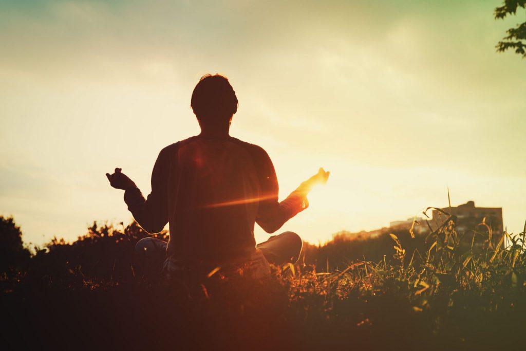 Homem sentado na grama, ele está de costas com as pernas cruzadas e há a luz do sol ao fundo.