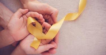 Mãos de uma criança em cima de uma mão de um adulto segurando fita amarela