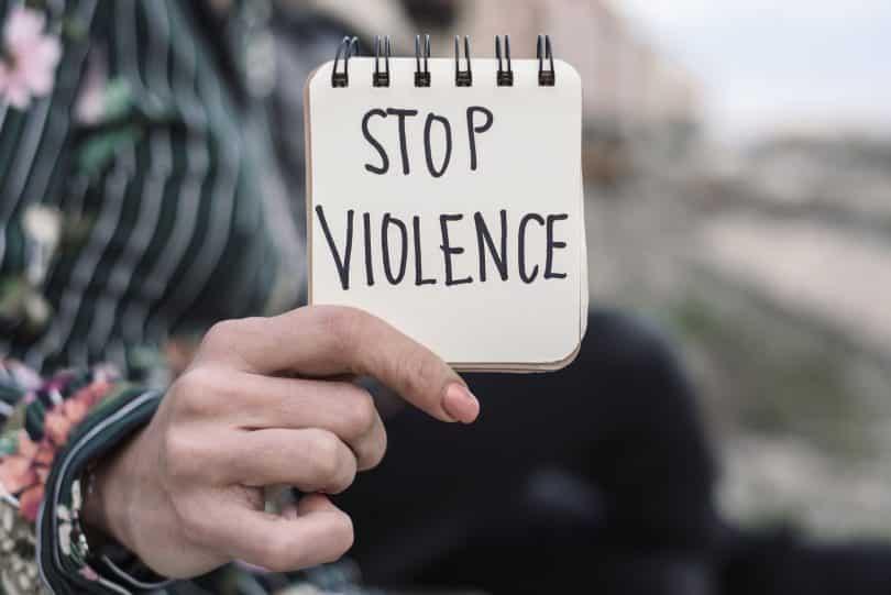 """Mão branca feminina segurando bloco de notas com o texto em inglês, traduzido: """"Pare a violência"""""""