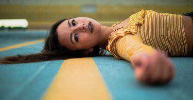 Garota morena deitada no chão de uma quadra de esportes. Ela está usando uma blusa amarela com listras brancas.