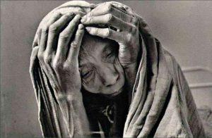 Foto em preto e branco, Sebastião Salgado. Close de pessoa com feições pesadas. As mãos envelhecidas com veias aparentes emolduram o rosto, amassam a pele ressecada e enrrugada. Um tecido envolve a cabeça como um manto.