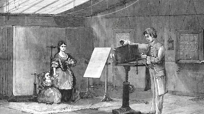 Ilustração em preto e branco mostra uma cena antiga: o fotógrafo ajusta a câmera de pedestal, o Daguerreótipo, enquanto a senhora posa com a criança.