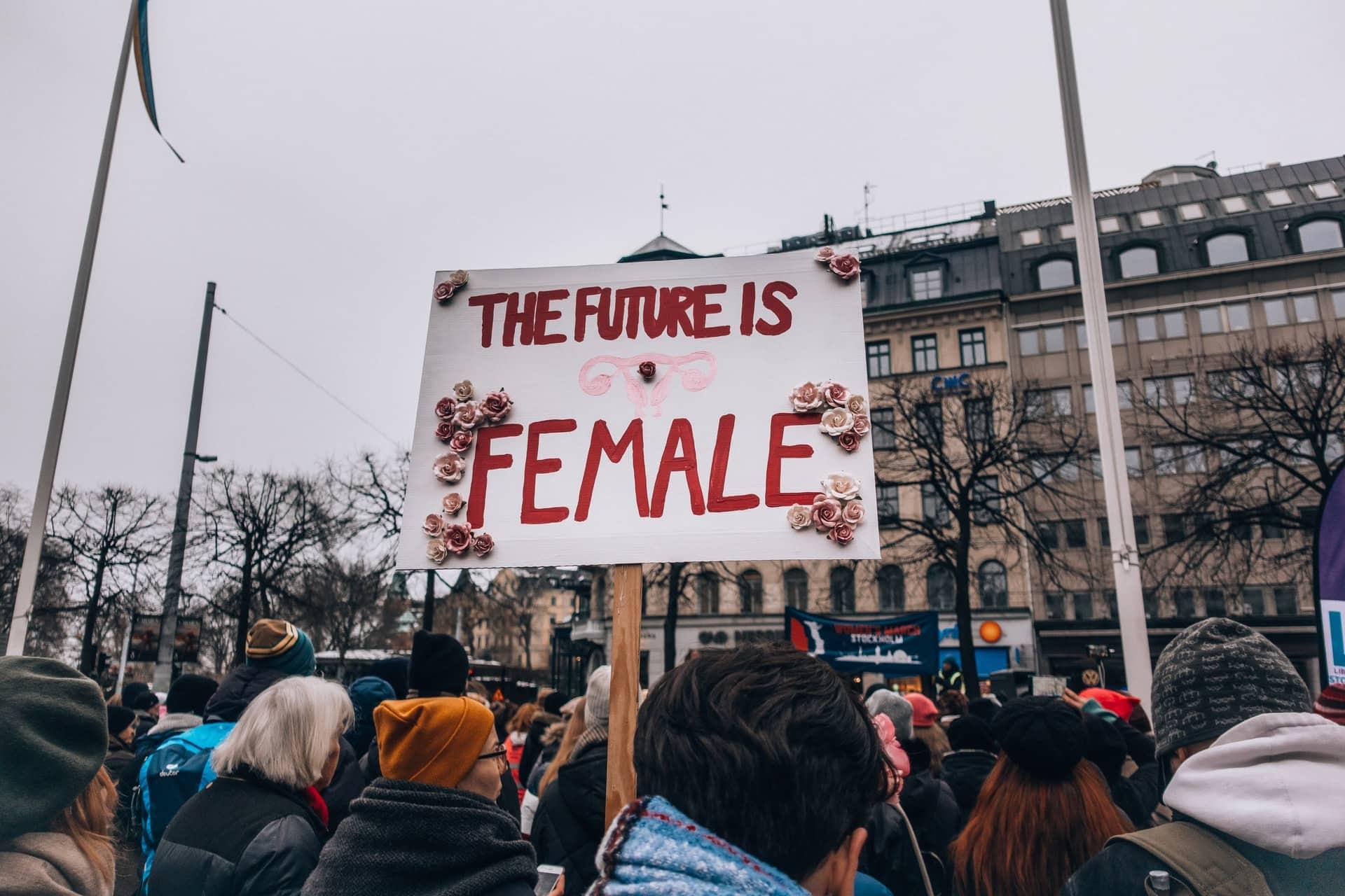 """Cartaz com o texto """"The future is female"""" com flores ao redor."""