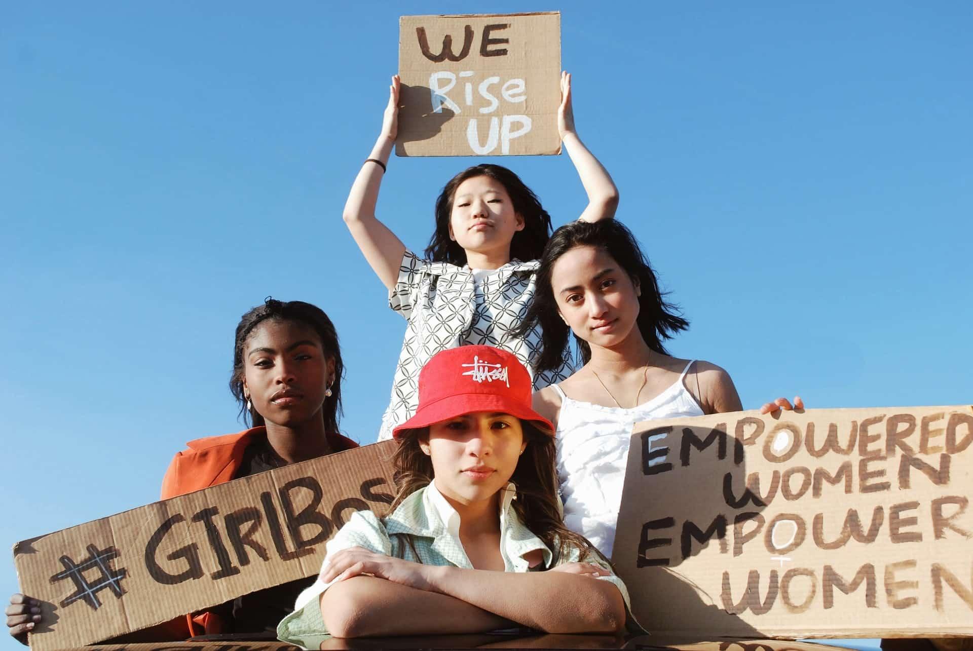Mulheres de diferentes etnias segurando cartazes.