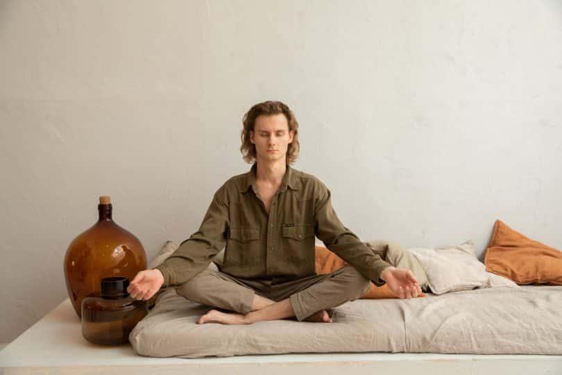 Homem sentado em um colchão de olhos fechados, meditando