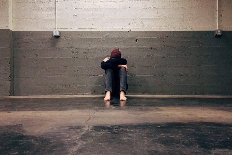 Homem sentado no chão abraçando seus joelhos