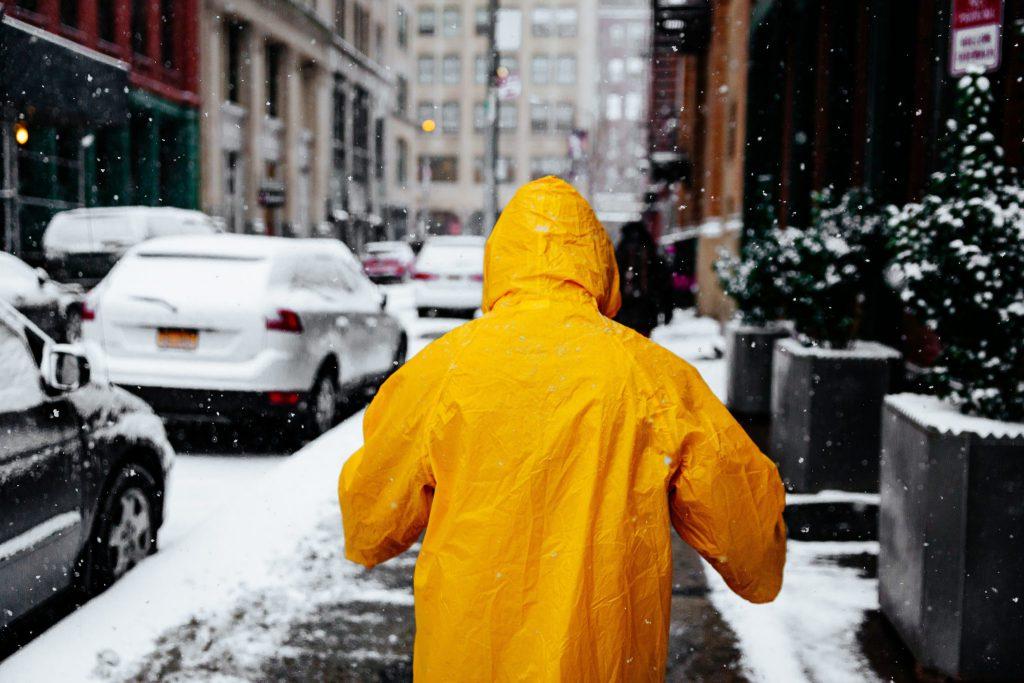 Homem de costas vestindo uma capa de chuva amarela. Ao fundo o cenário é de uma rua com carros estacionados e cobertos pela neve.