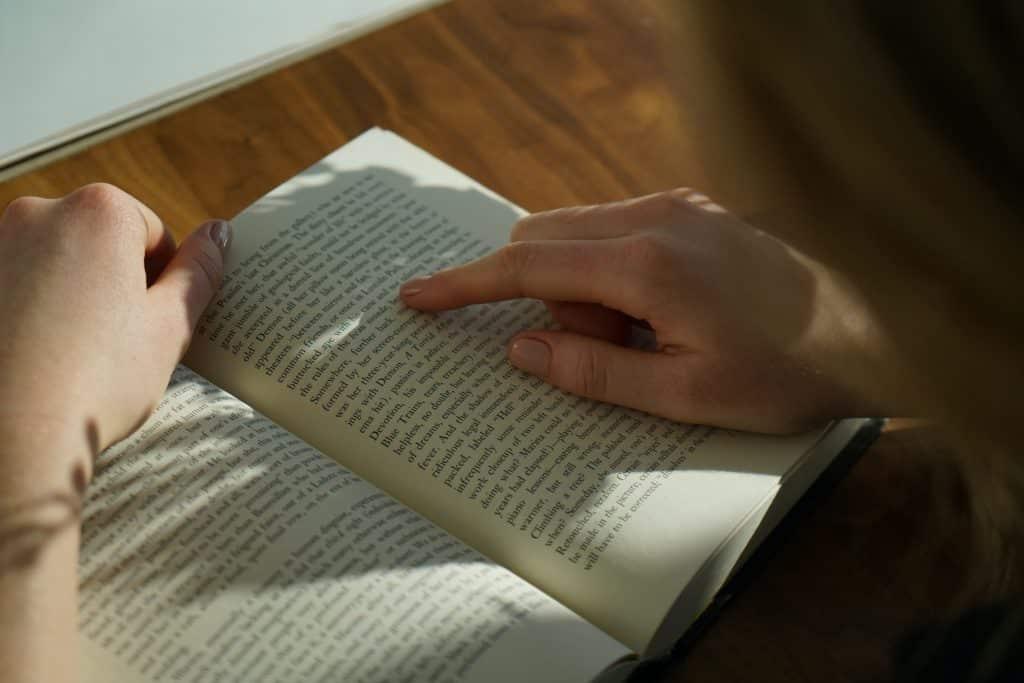 Mulher lendo livro com o reflexo do sol