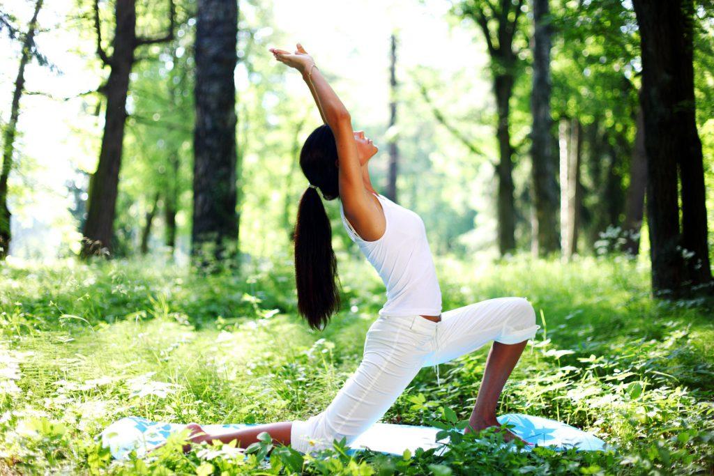 Uma mulher vestida com uma calça branca e uma regata branca. Ela está em meio a um bosque, fazendo uma posição de yoga em que ela está apoiada em um joelho e flexionando o outro, enquanto os dois braços estão esticados para cima. A mulher é morena e tem cabelos pretos presos em um rabo de cavalo.