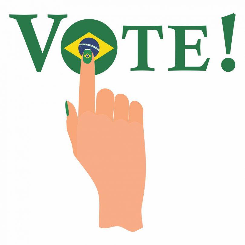 Desenho de uma mão apertando a palavra voto pintada com a bandeira do brasil.