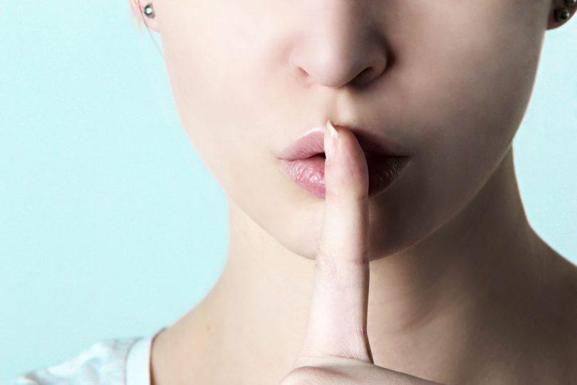 O fundo da imagem é azul claro. Em primeiro plano há o rosto de uma mulher visto apenas do nariz para baixo até os seus ombros. Ela está fazendo um bico com a boca e tem seus cabelos presos, não sendo possível vê-los. Ela está com o dedo indicador na frente da boca como se indicasse silêncio.