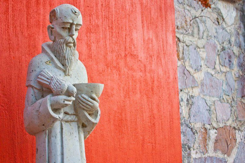 Estátua de São Francisco de Assis no lado de fora de uma igreja.