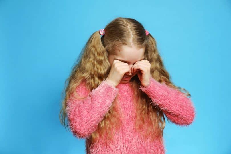 Menina chora com as mãos sobre os olhos.