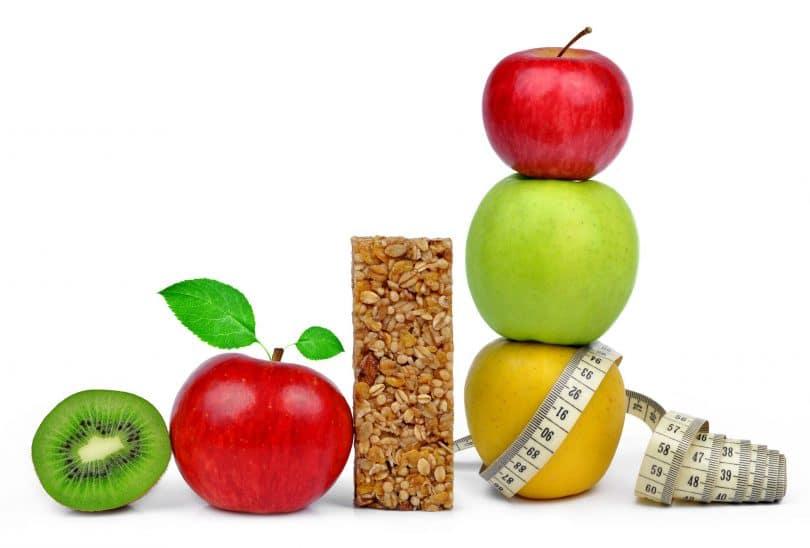 Frutas juntas, maçãs, kiwis, peras, perto de uma barrinha de cereal e uma fita métrica.