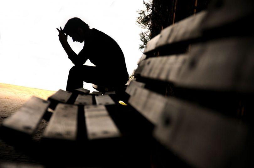 Sombra de um homem sentado em um banco de praça, apoiando a cabeça nas mãos.