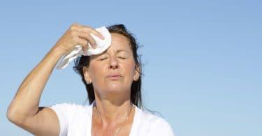 Mulher idosa, vestida de branco com os olhos fechados, cabelo ao vento, secando a testa com um pano branco, com um céu azul ao fundo.