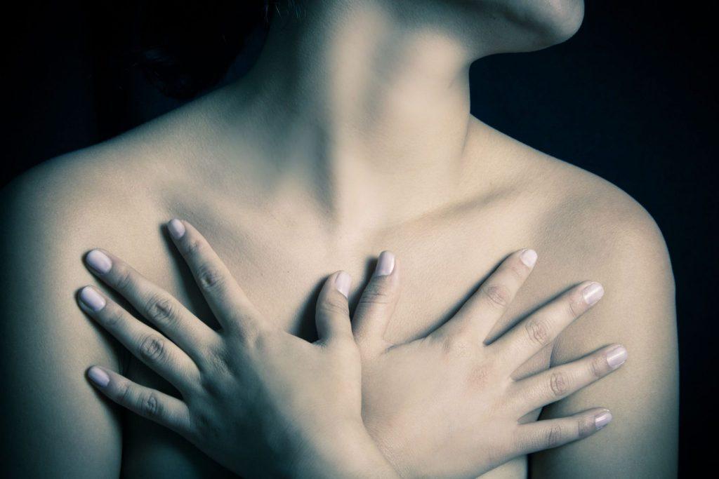 Imagem que foca no colo de uma mulher. Ela está com as duas mãos por cima dos seios e dessa forma os cobre. A foto é escura e o fundo é preto.