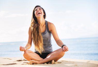 Mulher sentada em pose de meditação. Ela está sentada na areia, ao fundo há um oceano e a mulher está sorrido enquanto olha para cima.