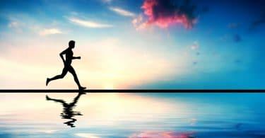 Silhueta de pessoa correndo em frente à um céu colorido e com seu reflexo aparecendo na água .