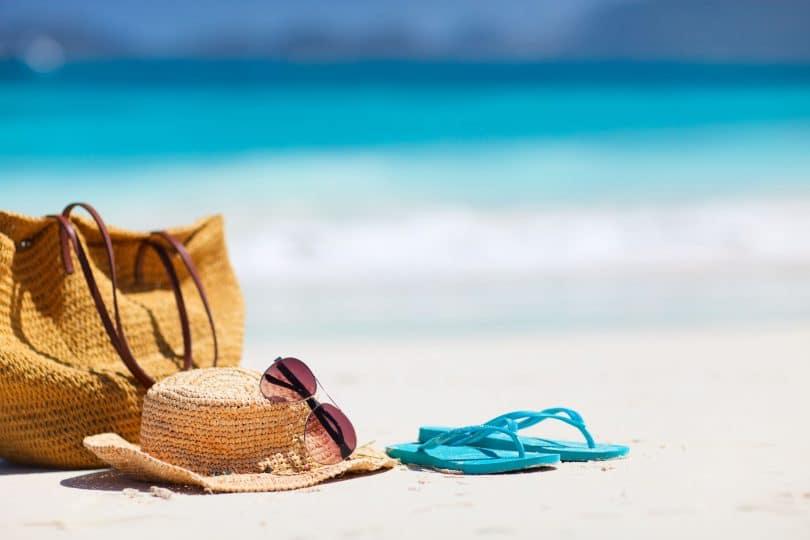 Bolsa, chapéu de palha, óculos de sol e chinelo azul em areia da praia, com mar ao fundo.