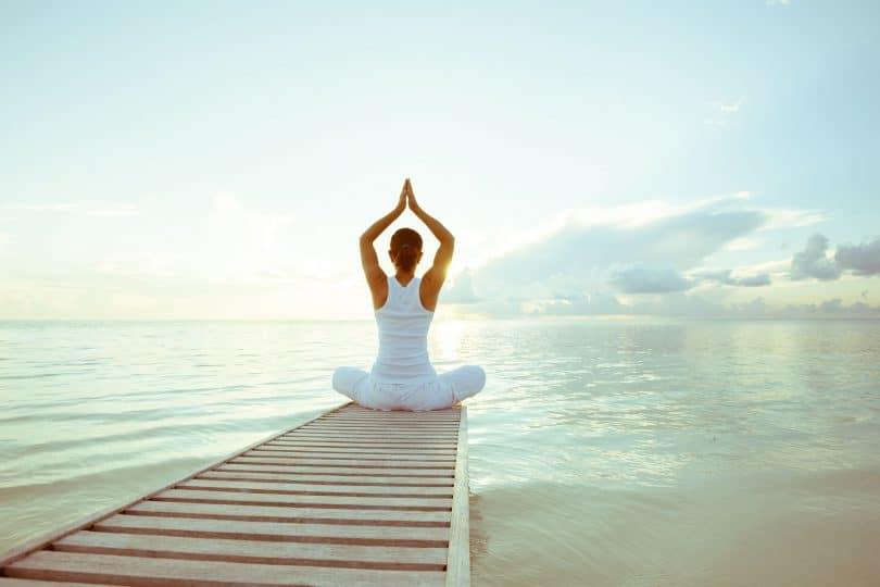 Mulher branca sentada em uma posição de yoga em cima de um pier em frente ao mar.