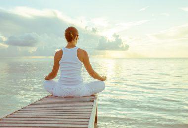 Mulher sentada em cima de um pier, com as pernas cruzadas de frente para o mar.