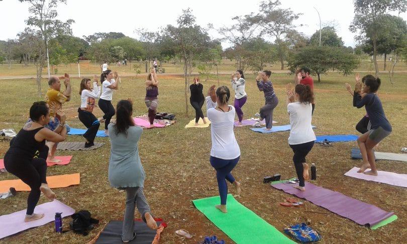 Grupo de pessoas em um parque, organizadas em circulo, praticando ioga.