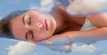 Mulher dormindo em uma cama azul claro de nuvens.