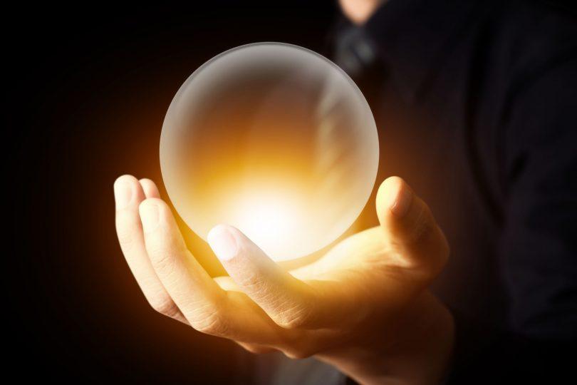 Mão de um homem branco segurando uma bola de cristal iluminada.