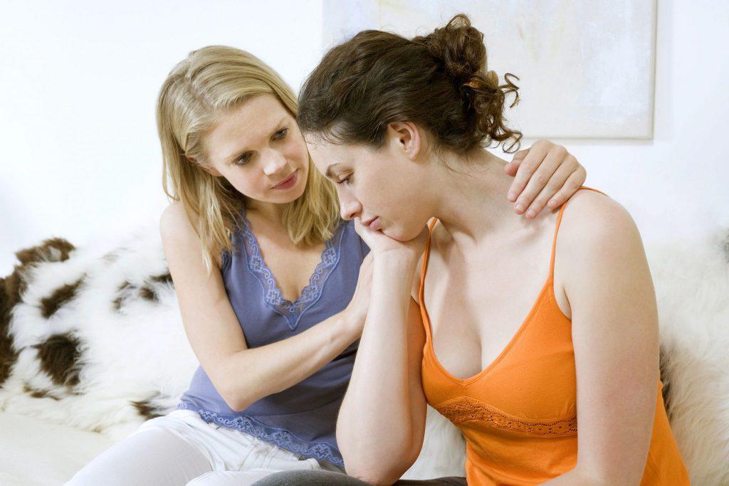 Duas mulheres sentadas em um sofá. Uma está aparentemente triste e a outra está confortando ela.
