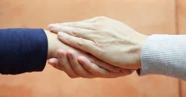 Par de mãos femininas segurando a mão de outra pessoa.